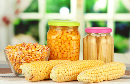 Fresh, canned and dried corn on wooden table, on bright background photo