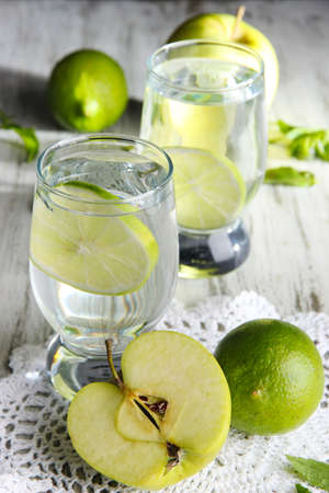 Glasses of cocktail with lime on napkin on light wooden table photo