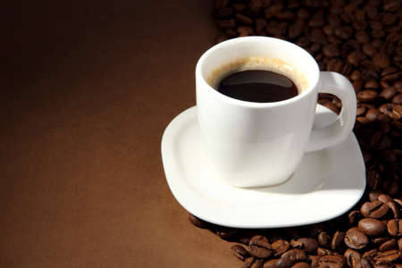 mocca: Cup of coffee with coffee beans on brown background