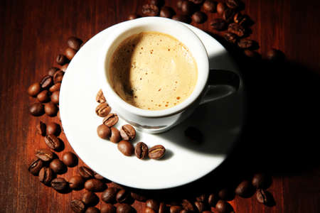 mocca: Cup of coffee with coffee beans on wooden background