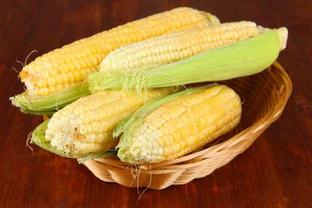 Fresh corn vegetable in wicker basket on wooden table photo