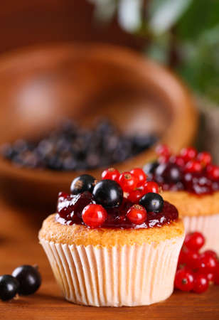 cup cakes: Tasty muffins with berries on wooden table