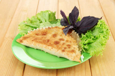 Tasty chebureks with fresh herbs on plate,on wooden background photo