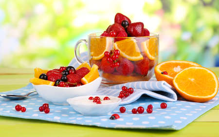 exotics: Useful fruit salad in glass cup and bowl on wooden table on natural background