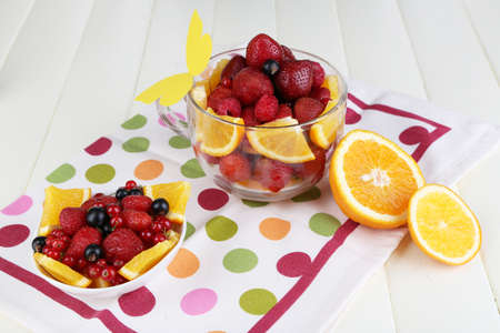 Useful fruit salad in glass cup and bowl on wooden table close-up photo