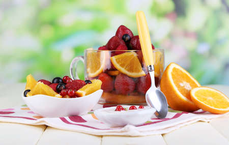 Useful fruit salad in glass cup and bowl on wooden table on natural background photo