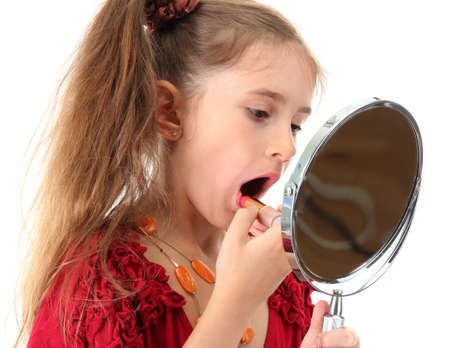 little girl in her mother's dress, is trying painting her lips, isolated on white photo