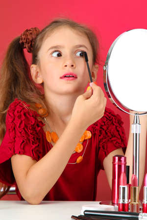 little girl in her mothers dress, is trying painting her eyelashes photo