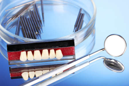 denture with dental tools on blue background photo
