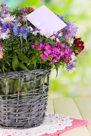 Beautiful bouquet in basket on wooden table on natural background photo