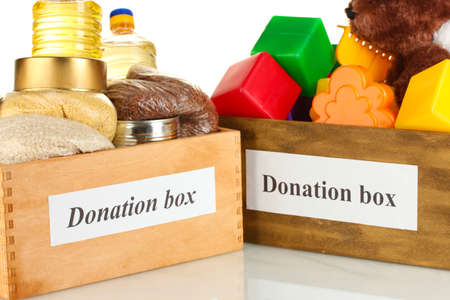 Donation box with food and childrens toys on white background close-up photo