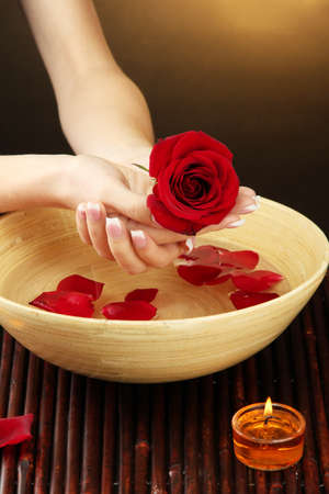 handcare: woman hands with wooden bowl of water with petals, on brown background