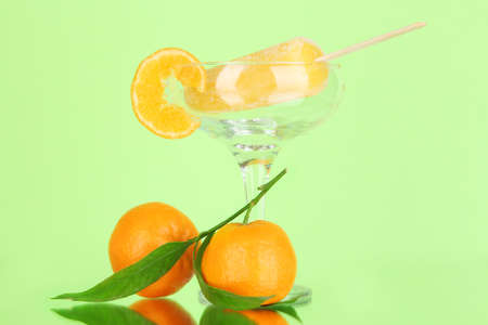 Yellow fruit juice ice in vase on green background photo