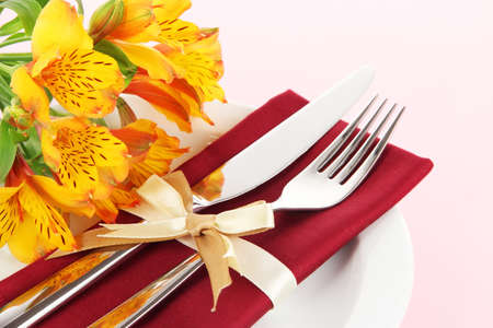 Festive dining table setting with flowers on pink background photo