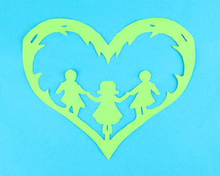 Green cut out paper heart with people inside, on color background photo