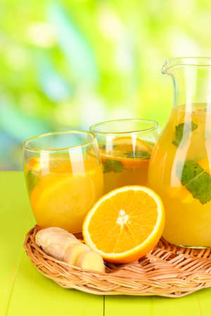 Orange lemonade in pitcher and glasses on wooden table on natural background Stock Photo - 21034260