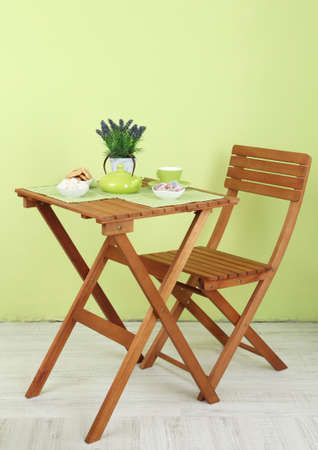Wooden table with tea table setting on it in room photo