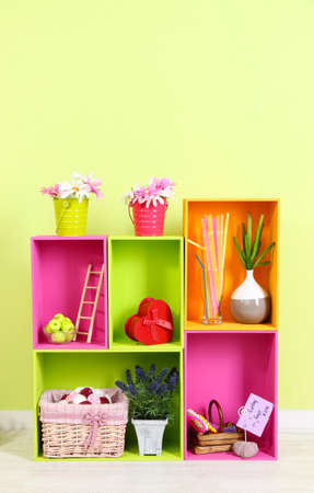Shelves of different bright colors with decorative addition on wall background photo