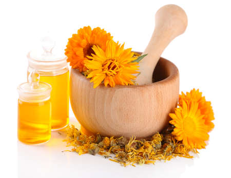 Medicine bottles and calendula flowers in wooden mortar isolated on white