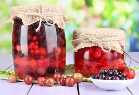 Home made berry jam on wooden table on bright background photo