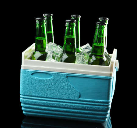 Bottles of beer with ice cubes in mini refrigerator, on black background photo