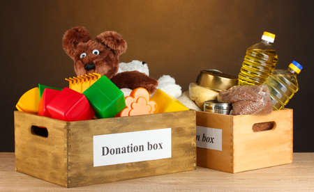 Donation box with food and childrens toys on brown background close-up photo