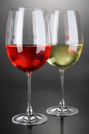 Red and white wine in glasses on grey background photo