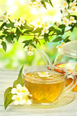 Cup of tea with jasmine, on wooden table, on bright background photo