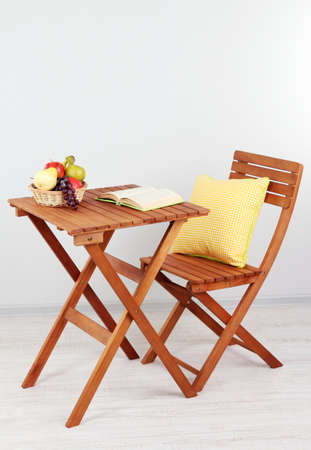 Wooden table with fruit and book on it in room photo