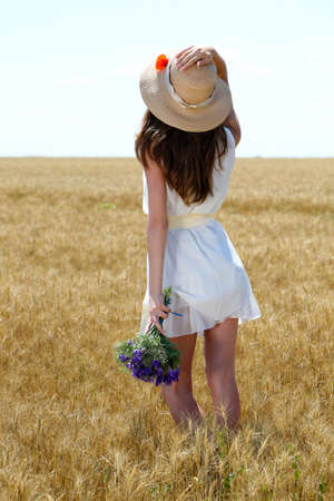 Portrait of beautiful young woman with flowers in the field photo