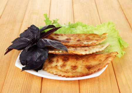 Tasty chebureks with fresh herbs on plate,on wooden background Zdjęcie Seryjne