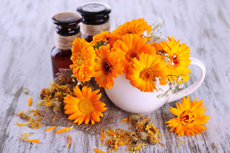 Medicine bottles and calendula flowers on wooden background photo