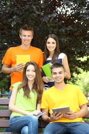 Happy group of young students sitting in park Stock Photo - 21203601
