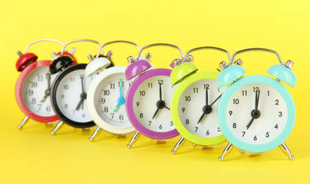 Colorful alarm clock on yellow background photo