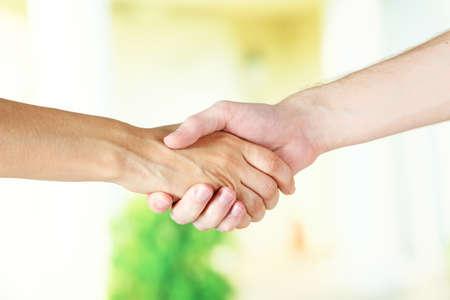 negotiating: Handshake on light background