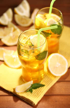 Iced tea with lemon and mint on wooden table, outdoors photo