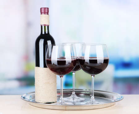 Wine glasses and bottle on bright background photo