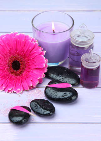 Spa stones, beautiful gerbera and candle on wooden table photo