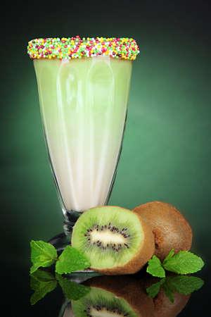 Delicious milk shake on dark green background photo