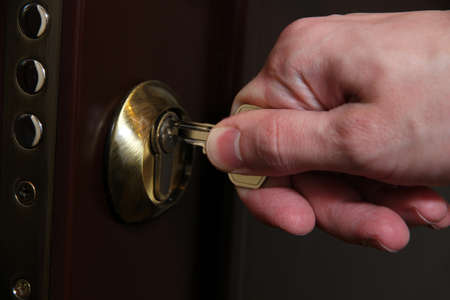 opens: Someone opens door key close-up Stock Photo