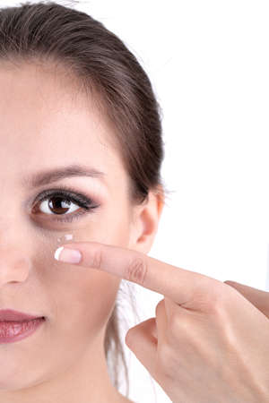 lentes de contacto: Mujer joven que pone la lente de contacto en el ojo de cerca