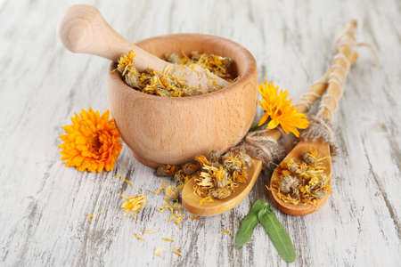 Fresh and dried calendula flowers in mortar on wooden background photo
