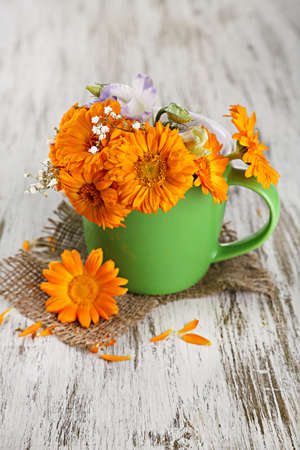 Calendula flowers in cup on wooden background photo