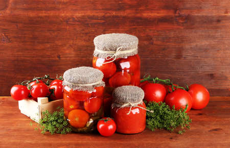 sterilized: Tasty canned and fresh tomatoes on wooden table Stock Photo