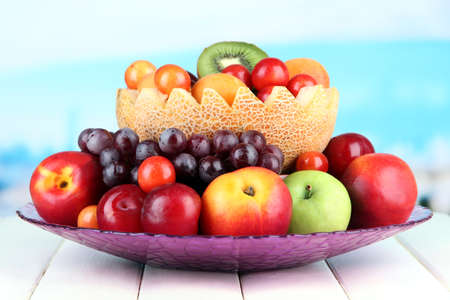Assortment of juicy fruits on wooden table, on bright background photo