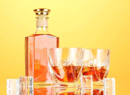 whisky bottle: Bottle and two glasses of scotch whiskey, on color background