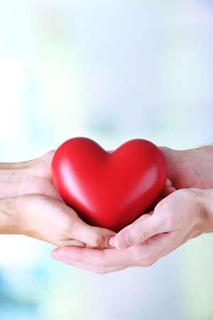 chăm sóc sức khỏe: Trái tim trong tay trên nền ánh sáng