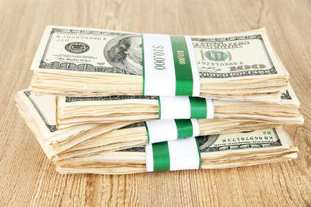 Stacks of money on wooden table photo