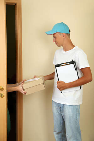 Young delivery man giving parcel photo