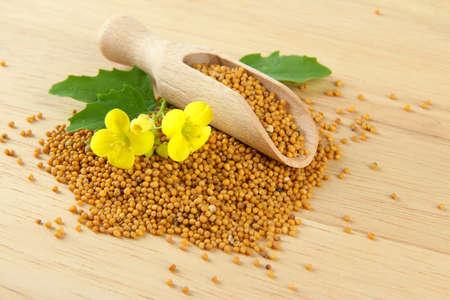 mustard leaf: Mustard seeds with mustard flower on wooden background Stock Photo